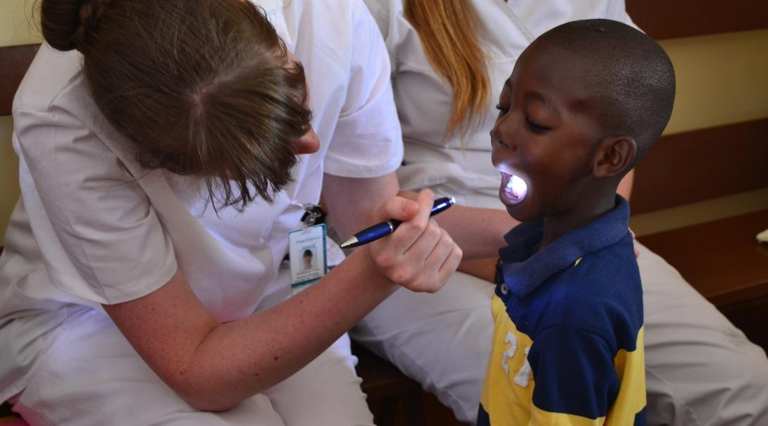 Projects Abroad female Dentistry intern examines a childs mouth with a torch during an Outreach programme within a Dentistry placement in Jamaica.
